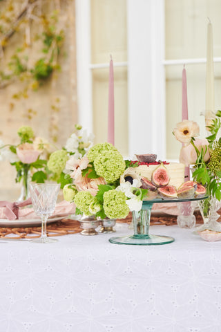 Tablescape featuring cake decorated with cut figs and flowers
