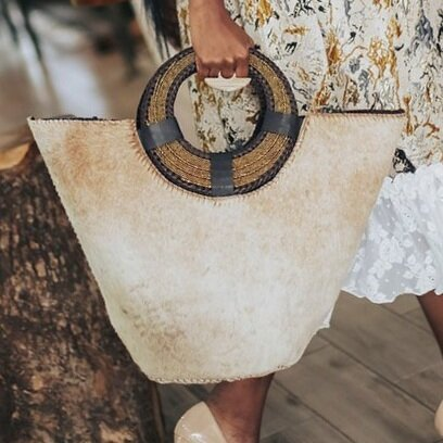 Our Oversized Hide Kikapu is an update on the classic Kikapu bag. It is handcrafted in Nairobi, Kenya by our local artisan and features a genuine cowhide body, unlined interior and hand beaded leather ring handles. All odAOMO bags are designed by Dr. Sophia Aomo Omoro and produced in limited quantities.