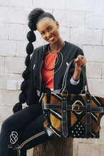 Load image into Gallery viewer, Our mudcloth weekend bag is the perfect carryall for weekend getaway. This bag is handcrafted in Nairobi, Kenya by our local artisan using eco-friendly and sustainable materials and all leathers are byproducts from local farms. Each piece is designed by Dr. Sophia Omoro and produced in limited quantities.