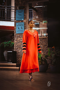 Our Hibiscus Silk Crepe Tunic Dress is handmade in Ghana using eco-friendly and sustainable materials. It features a round neckline and a blouson sleeve with contrast velvet detail. It is shown here with our Saturn Choker. odAOMO garments are designed by Dr. Sophia Omoro and produced in limited quantities.