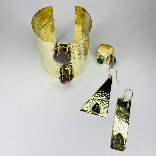 Our Nested Stone Collection is handcrafted in Kenya by our local artisan using 100% recycled brass and inlaid, polished semiprecious stones. The set includes one pair of earrings, one cuff and one ring. All materials used are eco-friendly and sustainable and no two pieces are the same! *Please note these items are handmade, so stone coloration/shapes will vary.