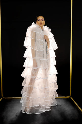 Our Floor Length Ruffle Cape is handmade in Ghana using fine nylon tulle and 100% cotton trim. The Elizabethan inspired collar creates a perfect frame for the face and the design of the body creates dramatic volume. The sheerness of the tulle keeps it light and airy. All odAOMO garments are designed by Dr. Sophia Omoro.