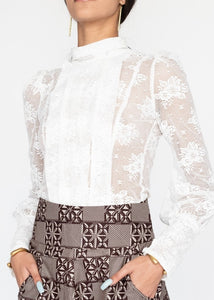 Our Lace Column Blouse is handmade in Kenya using imported Italian silk lace. It features a fabric covered button back closure, front box pleat detail, a puff shoulder and extended fabric covered button cuffs. All odAOMO garments are designed by Dr. Sophia Omoro and produced in limited quantities.