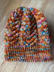 A photo of a knit cabled beanie that is mostly rust orange with pops of blue, pink and white throughout.