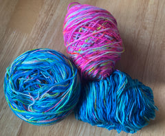 An image of three balls of hand dyed yarn lying on a wooden table.