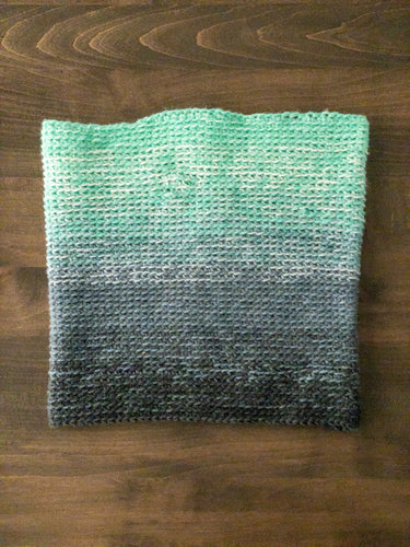 A photo of a crocheted cowl that is ombre dark grey, light grey, white and teal laying on a wooden table.
