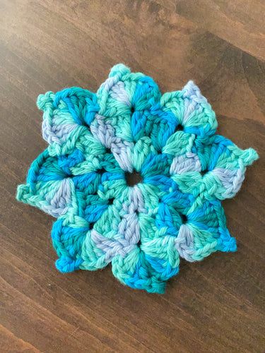 A photo of a hand knit flower shaped washcloth in shades of teal.