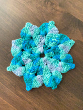 Load image into Gallery viewer, A photo of a hand knit flower shaped washcloth in shades of teal.
