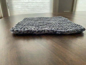 A knit potholder in tones of grays and white laying on a wooden table.