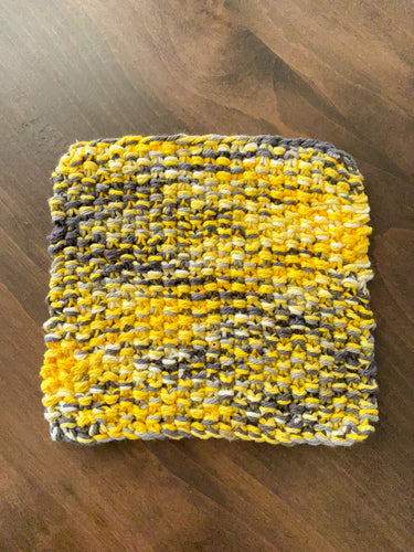 A knit potholder in tones of grays, yellows and white laying on a wooden table.