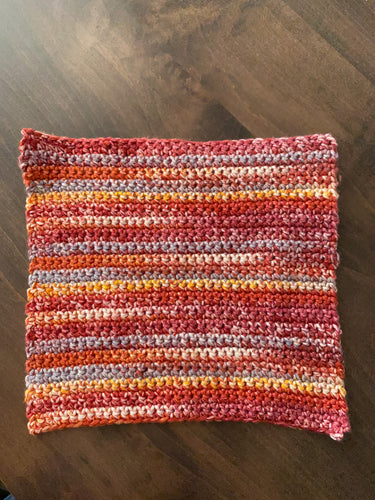 A photo of a hand knit washcloth in varying shades of red, yellow and white.