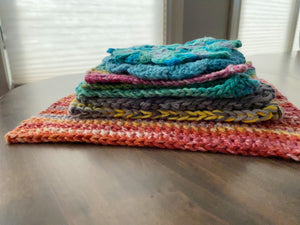 A pile of knit washcloths and potholders in various colors lying on a wooden table.