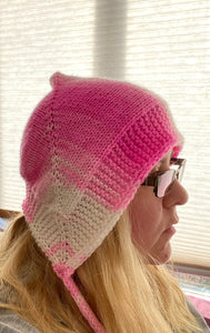 A photo of a pink and white bonnet on a blonde women's head.