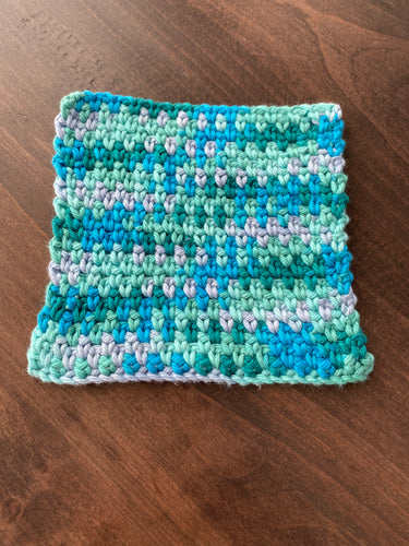 A hand knit washcloth in shades of teal and green.
