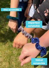 Load image into Gallery viewer, A photo showing three different styles of hand crocheted velvet scrunchies, the disc, imperfect and velvet.