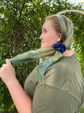 Load image into Gallery viewer, A photo of a woman wearing a hand crocheted velvet scrunchie around her pony tail, the photo is showing a side view.