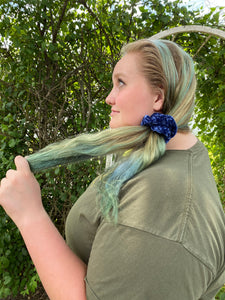 A photo of a woman wearing a hand crocheted velvet scrunchie around her pony tail, the photo is showing a side view.