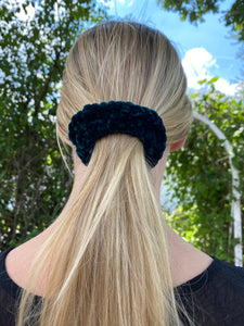 A close up photo of a woman wearing a hand crocheted velvet ponytail holder in her hair, the photo is a rear view.