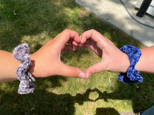 Photo of two hands with hand crocheted velvet scrunchies on their wrists, their fingers make a heart.