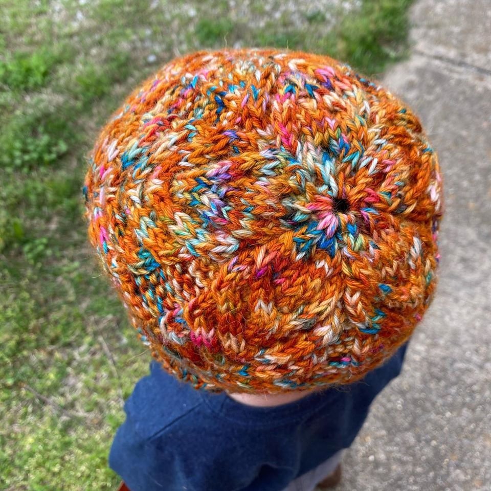 A photo of a little boy wearing a hand knit cabled hat in shades of burnt orange with pops of blue and purple and yellow and white.