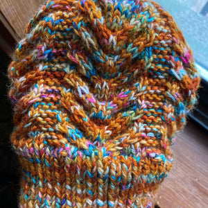 A closeup photo of a hand knit cabled hat in shades of burnt orange with pops of blue and purple and yellow and white laying on a window ledge.