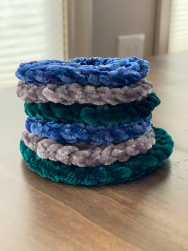 A photo of a stack of hand crocheted velvet scrunchies laying on a wooden table, the scrunchies are blue, gray or teal.