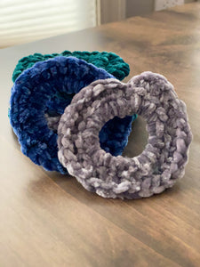 A side view photo of hand crocheted velvet scrunchies in blue, teal and gray laying on a wooden table.