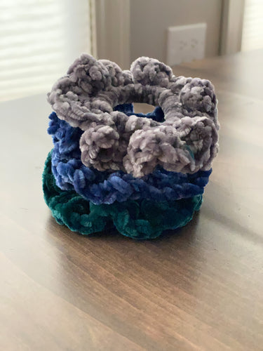 A stack of three imperfectly wavy scrunchies in gray, blue and teal.