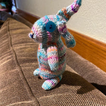 Load image into Gallery viewer, A photo of knit bunny in shades of teal standing on a couch.
