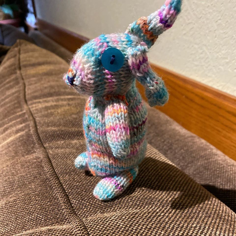 A photo of knit bunny in shades of teal standing on a couch.