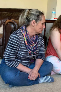 A photo of woman sitting on the floor wearing a hand knit shawl lying on a table, the shawl is navy with pink, orange and yellow running in stripes.
