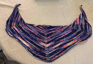 A photo of a hand knit shawl lying on a table, the shawl is navy with pink, orange and yellow running in stripes.
