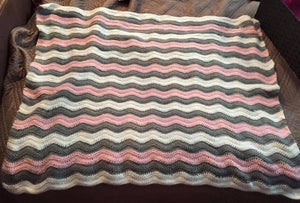 A photo of a hand crocheted baby blanket in undulating waves of white grey and pink.