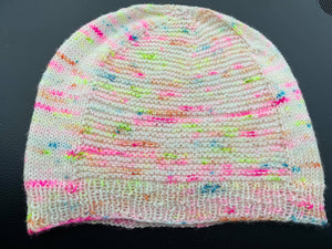 A photo of a knit beanie, the main color is a pale white with small neon color pops every few stitches.