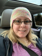 Load image into Gallery viewer, A photo of a blonde women wearing glasses and a handknit beanie, the main color is a pale white with small neon color pops every few stitches.