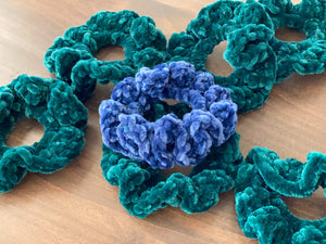 A pile of hand crocheted velvet scrunchies in various colors laying on a table.