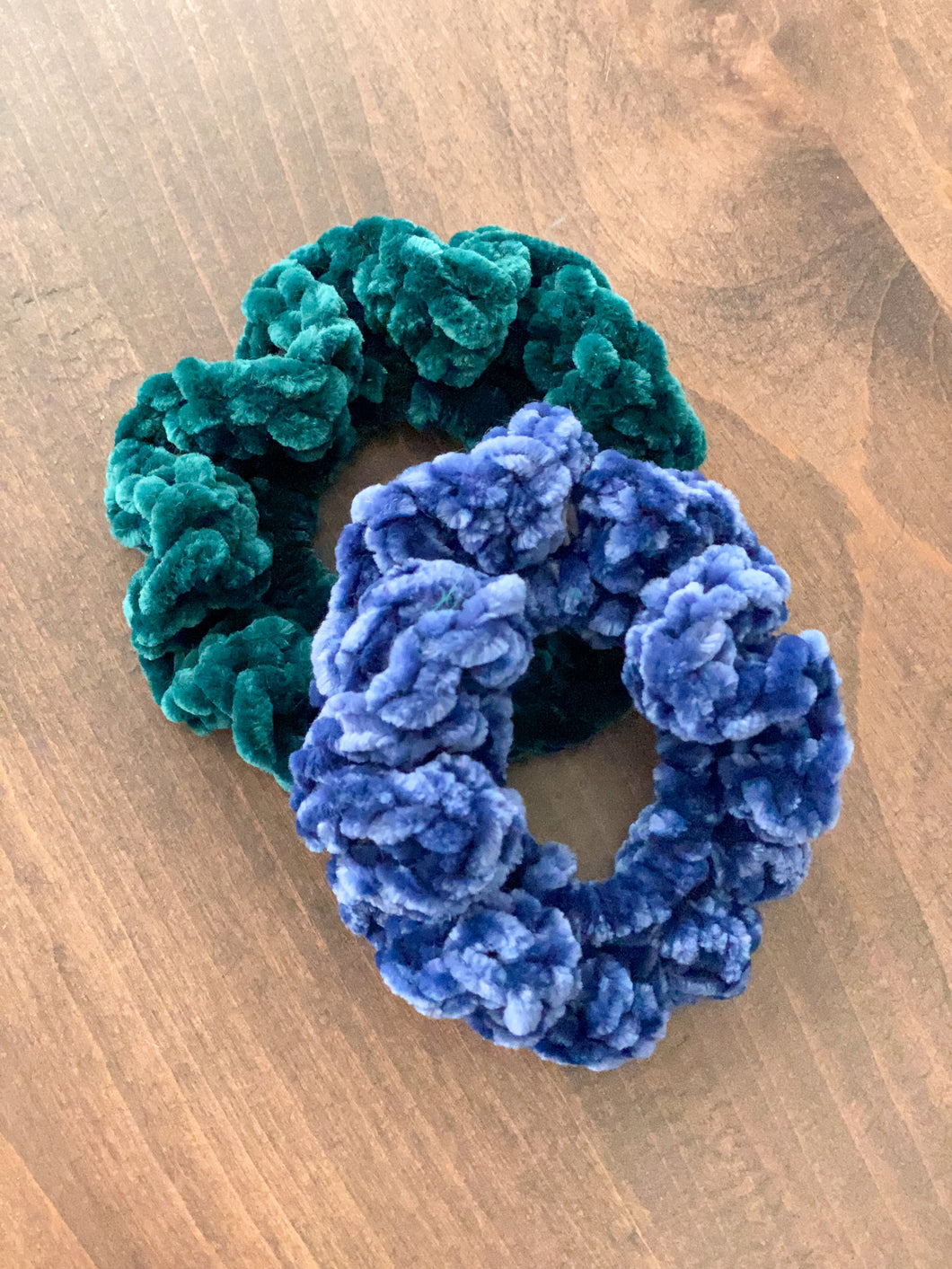 A photo of hand crocheted velvet scrunchies, one in blue and one in green laying on a wooden table.