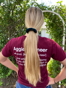A photo of a woman wearing a hand crocheted velvet ponytail holder in her hair, the photo is a rear view.