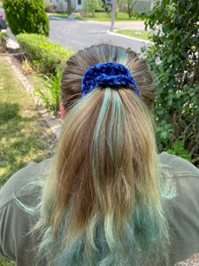 A rear view of a woman wearing a hand crocheted velvet scrunchie around her pony tail.