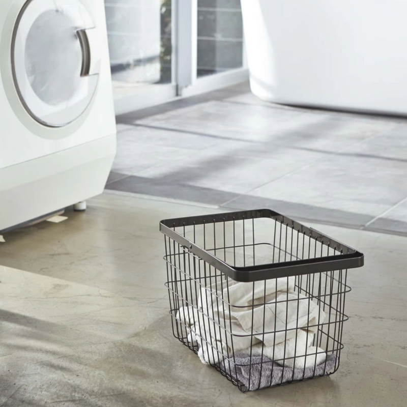 The elegant black medium Tower Laundry Basket is shown on the floor of the laundry room.
