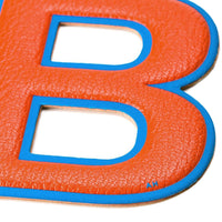 Anya Hindmarch Stickershop Oversized B Letter sticker in a clementine orange grained leather