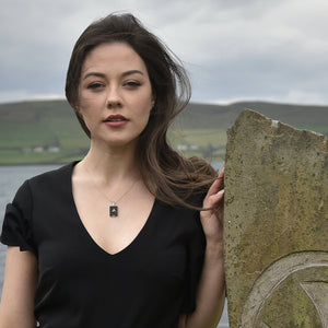 Model wearing Heritage necklace with Dingle Bay in the background