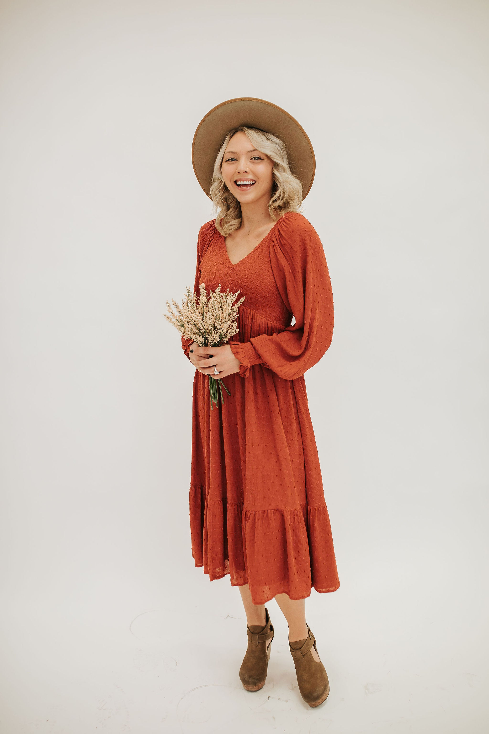 THE SCOUT SMOCKED SWISS DOT MIDI DRESS IN TERRACOTTA