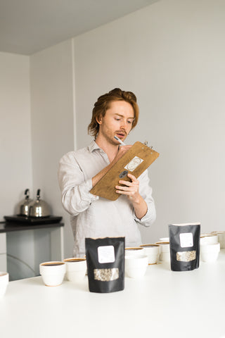 Cole Torode recording cupping results and coffee tasting notes