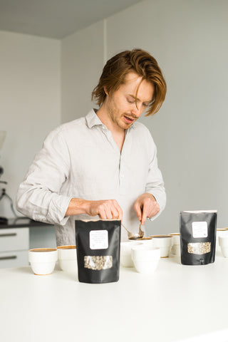 Cole Torode cupping coffee with cupping spoons