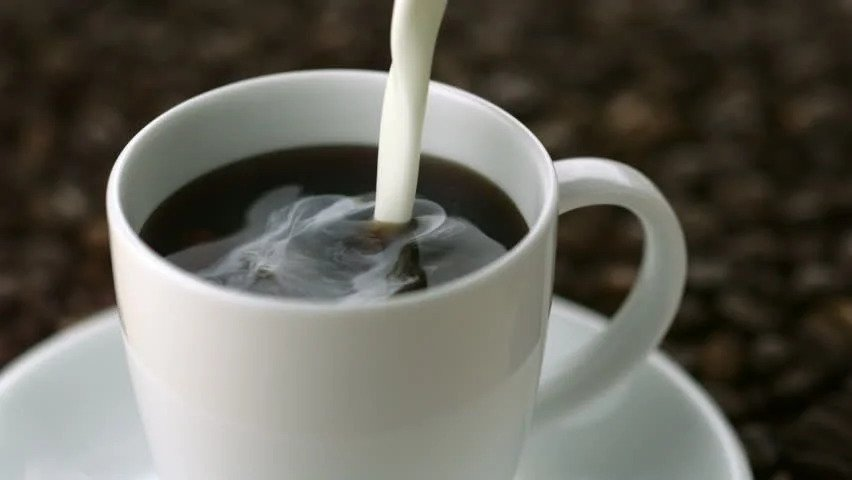 Pouring creamer in coffee and curdling