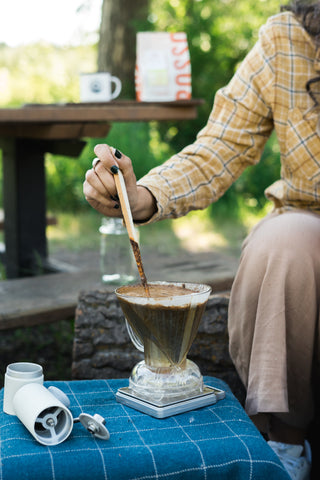 Stirring Clever Dripper coffee grinds with a stick