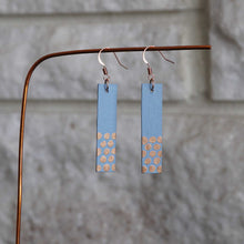 Load image into Gallery viewer, Rectangle dangle earrings made from recycled chipboard, hand painted in periwinkle blue and copper, and made with copper ear wire.