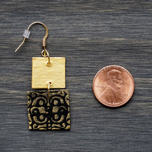 Load image into Gallery viewer, Two-tiered square dangle earrings made from recycled chipboard, hand painted in black and gold, and made with gold ear wire.