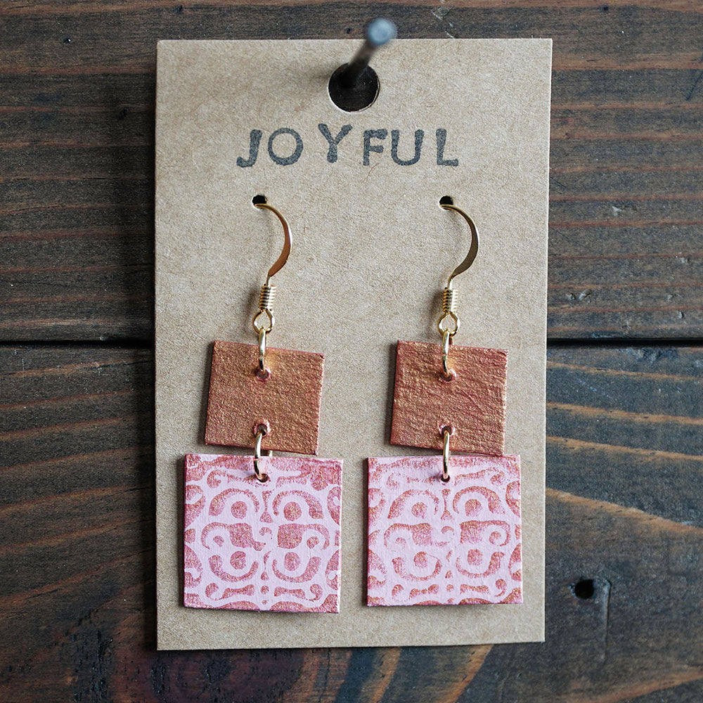 Two-tiered square dangle earrings made from recycled chipboard, hand painted in light pink and pink gold, and made with gold ear wire.